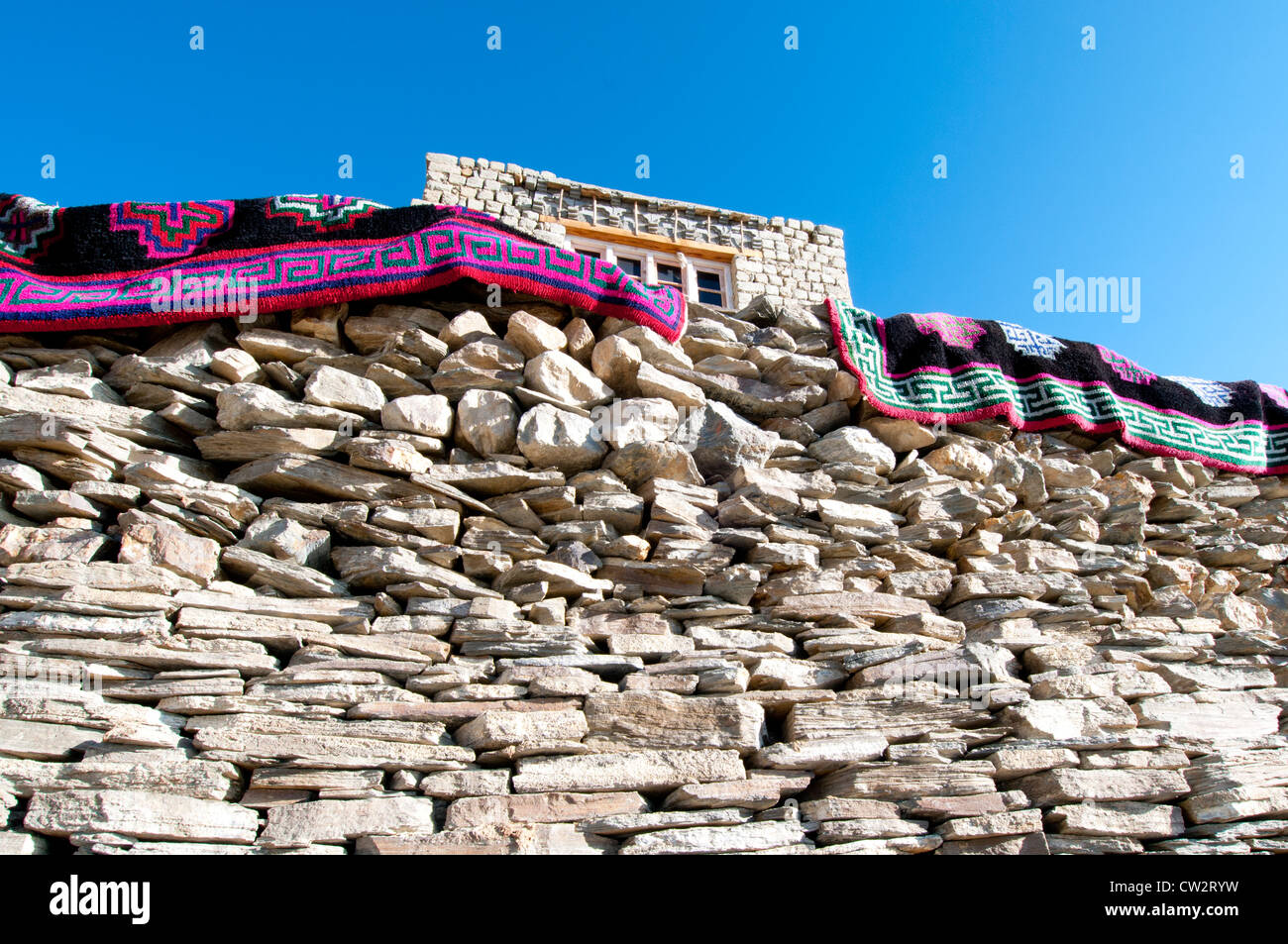 Two colorful patterned rugs hanging over a handmade stone wall with a house above in the village of Korzok, Ladakh, - Stock Image