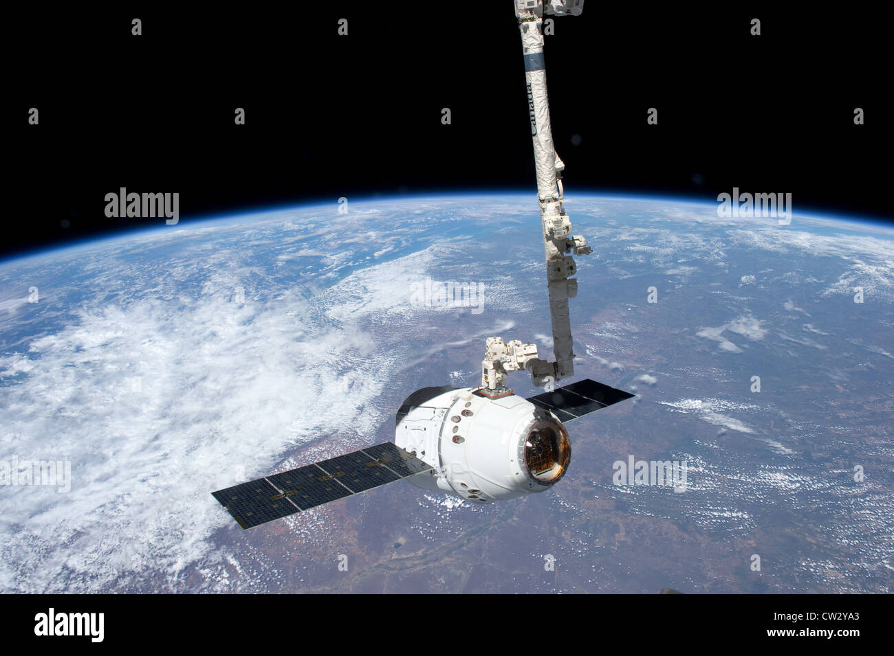 SpaceX Dragon commercial cargo craft grappled by the Canadarm2 robotic arm at the International Space Station Earth - Stock Image