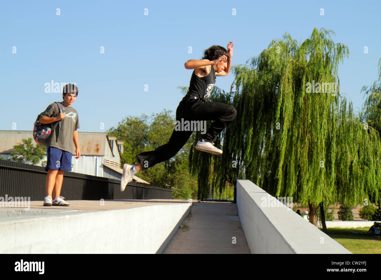 Mendoza Argentina Parque General San Martin public park pathway tree low wall Hispanic boy teen fitness sports freerunning - Stock Image