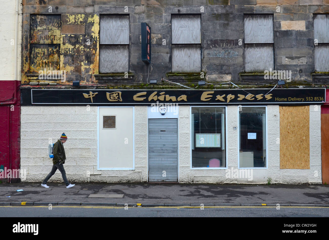 A lone figure walks by the China Express restaurant in a rather down at heel end of the Merchant City area of Glasgow. - Stock Image
