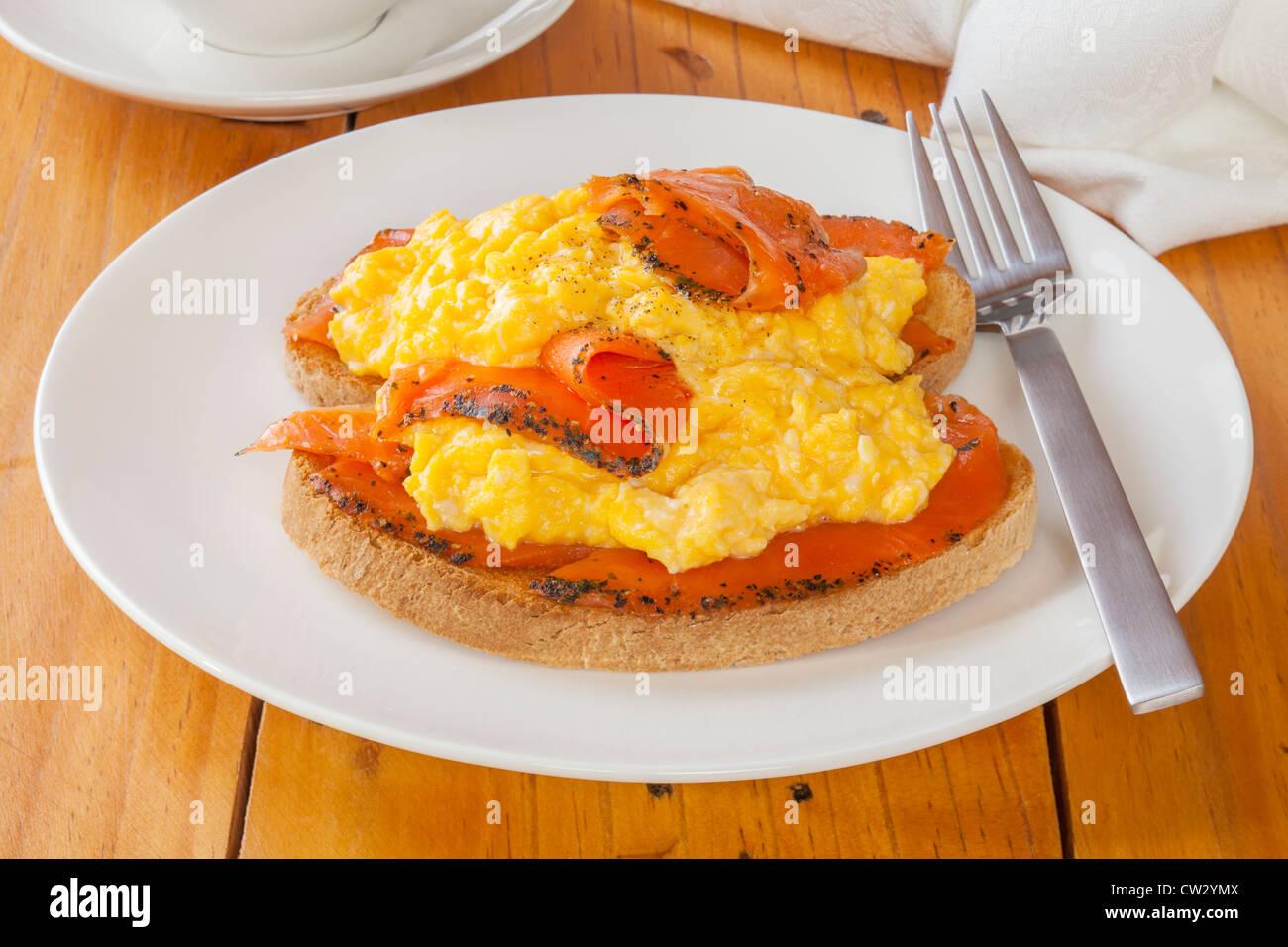 Seasoned smoked salmon with scrambled egg on toast. - Stock Image