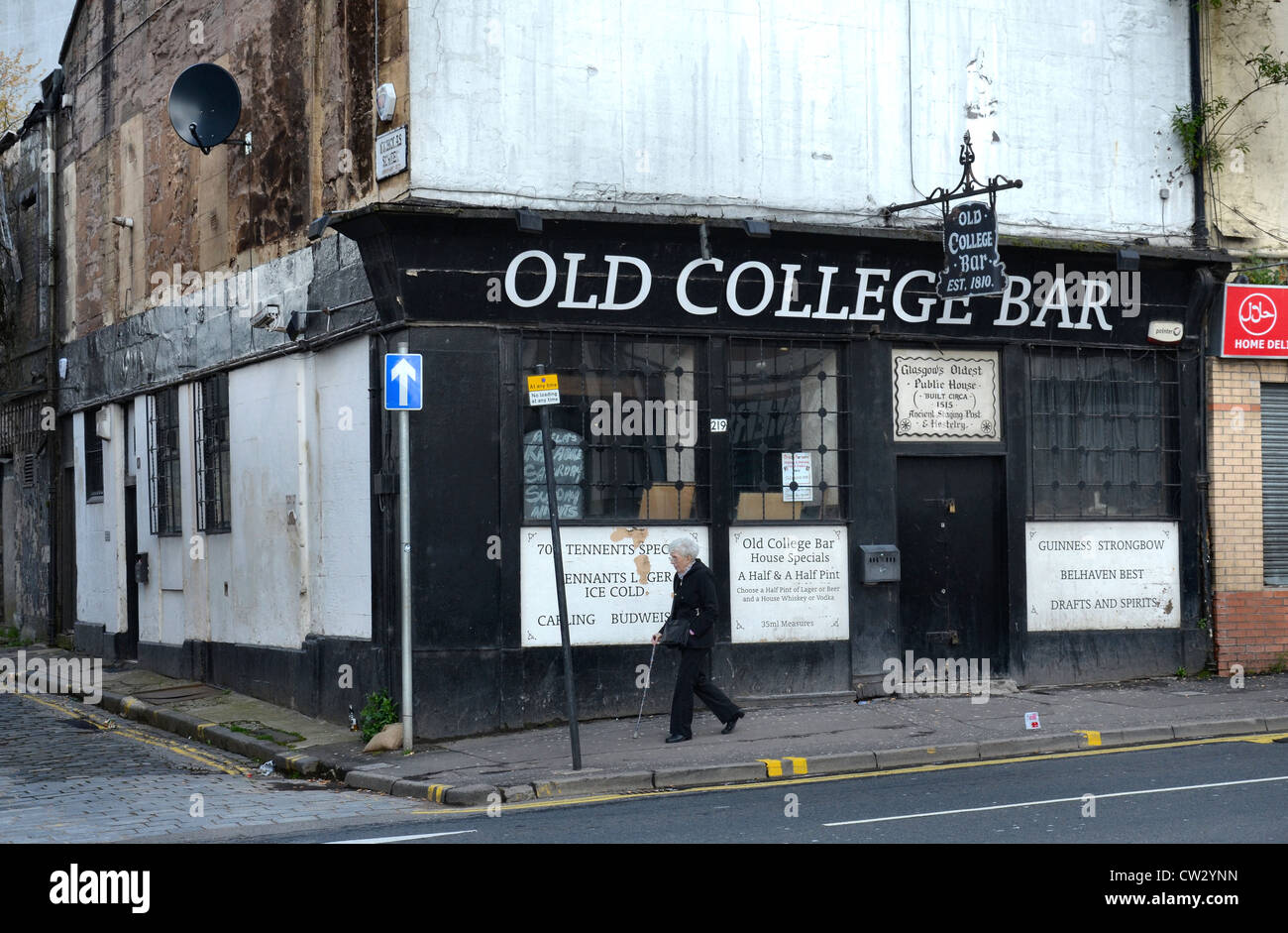 An elderly woman strolls by the Old College Bar (est. 1810) in Glasgow's High Street on the edge of the Merchant - Stock Image