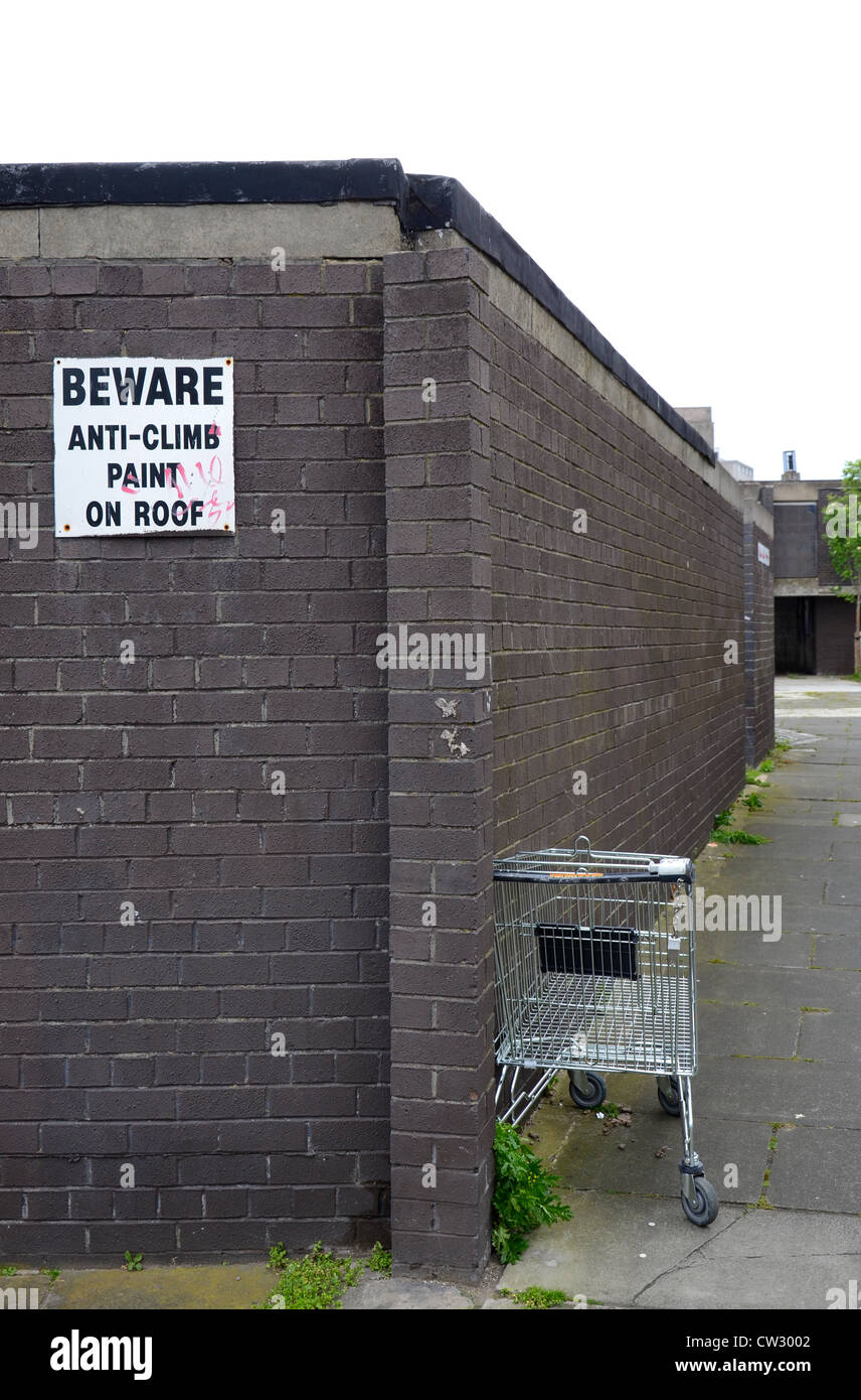 An abandoned supermarket trolley and a wall with a sign warning of anti-climb paint. - Stock Image