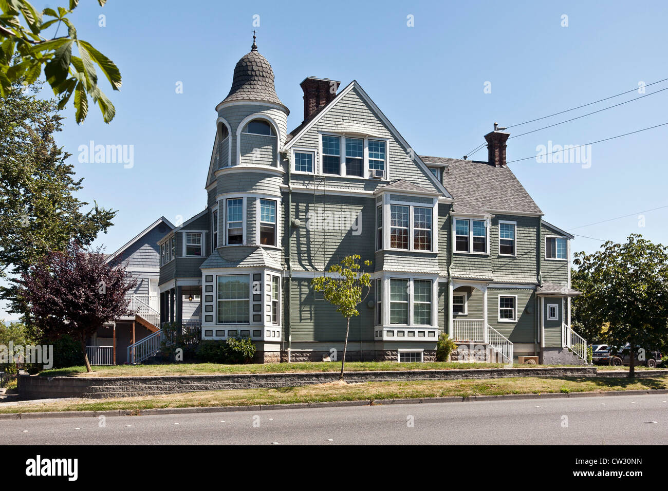 elegant old painted wood shingle Victorian house with bay windows & bell shaped cupola at corner Bellingham - Stock Image