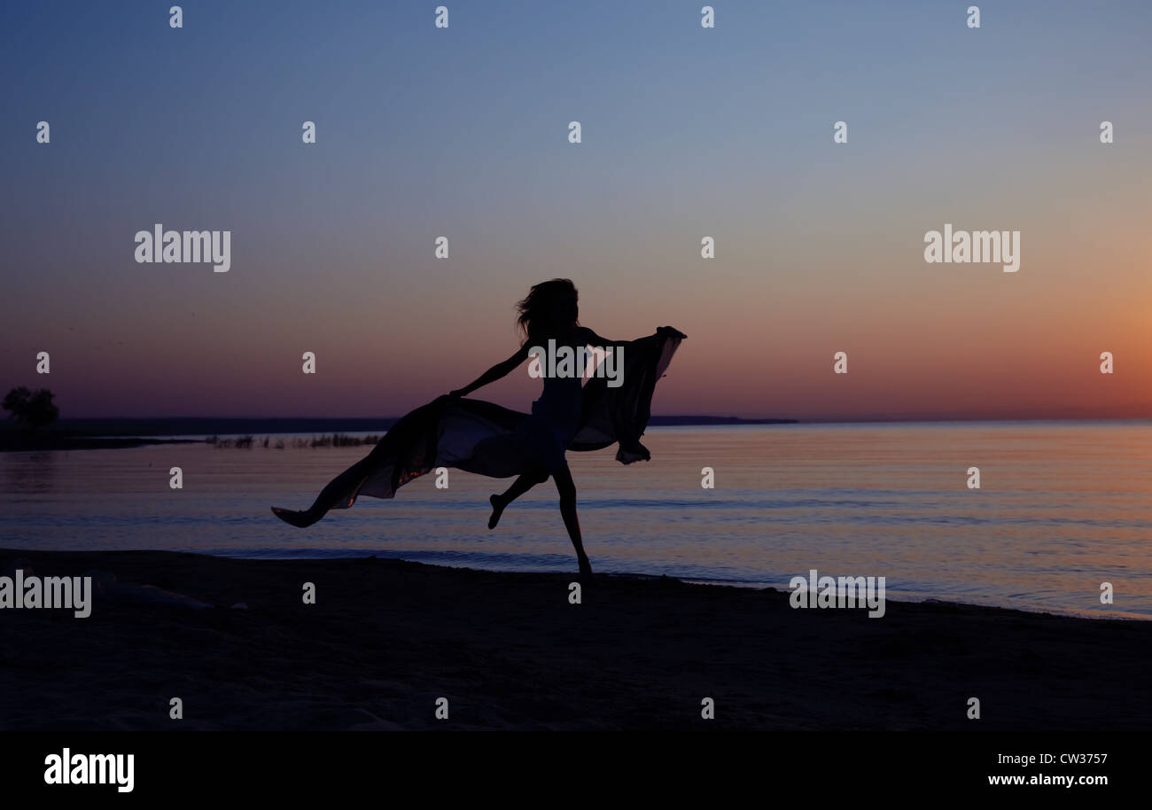 Silhouette of the woman flying at the sea during beautiful sunset. Natural light and darkness. Vibrant colors added - Stock Image