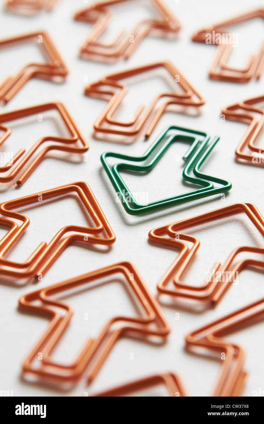Green Arrow Going Against The Flow Of Orange Arrows - Stock Image