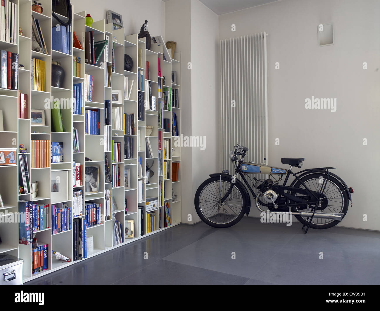 Living room in an italian apartment with an old motorbike parked - Stock Image