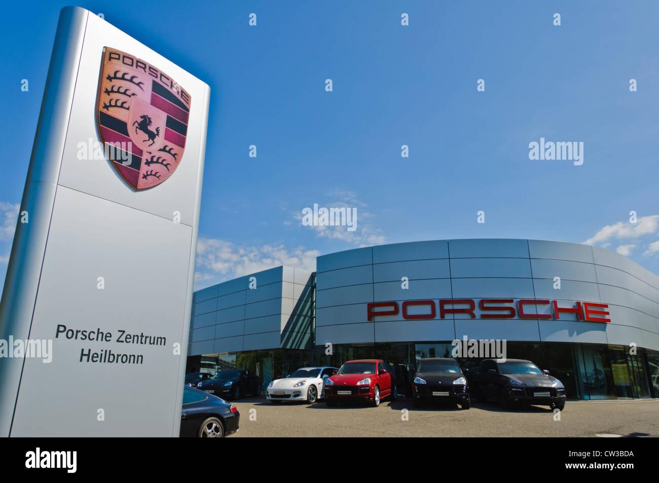 Porsche Zentrum Heilbronn company sign board with Porsche Logo in front of a modern Porsche luxury sports car dealership - Stock Image