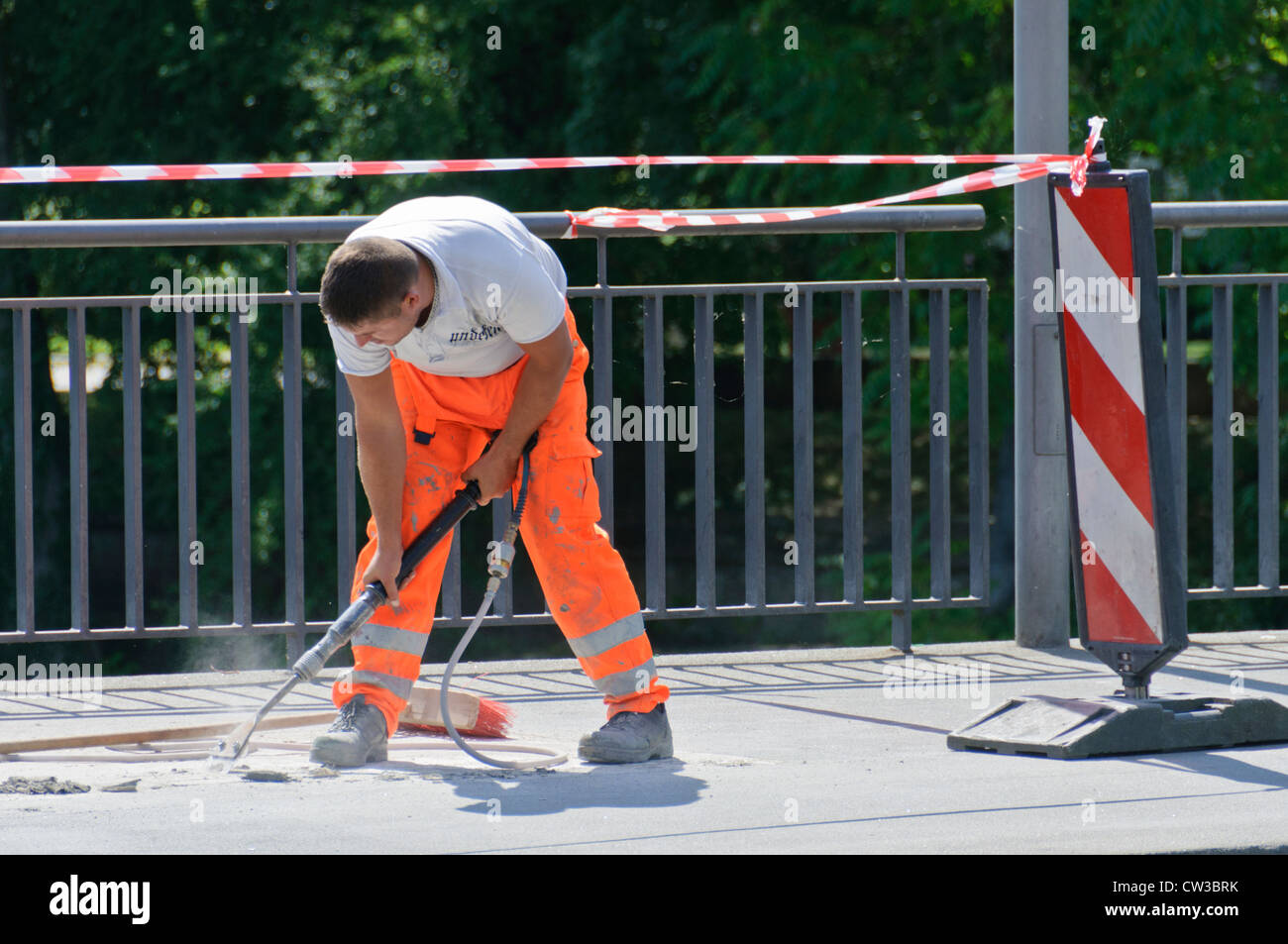 Construction worker wearing orange signal color work pants, working with a compressed air hammer on a bridge - Heilbronn Stock Photo