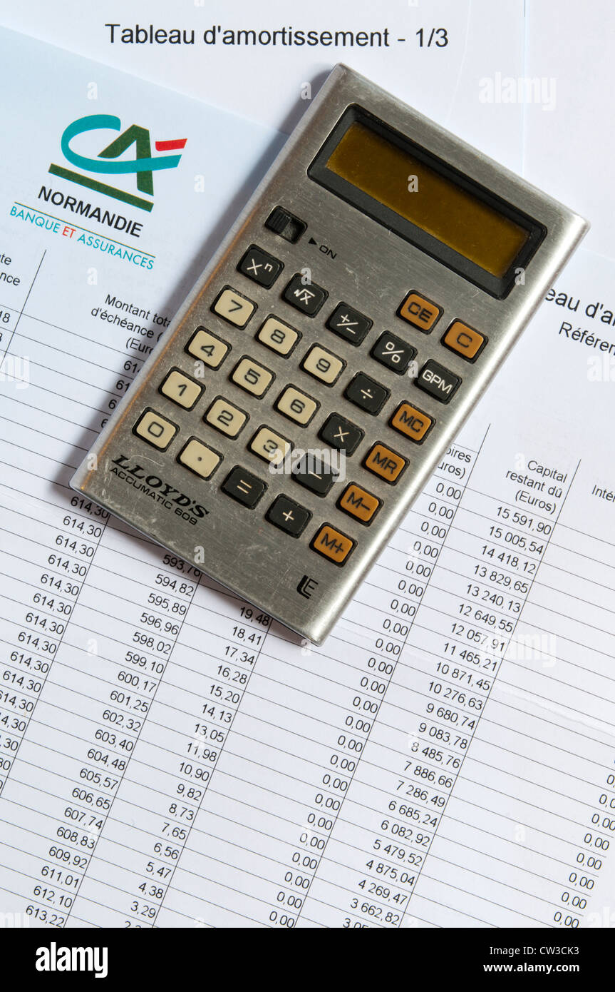 A pocket calculator laying on a mortgage repayment schedule. - Stock Image