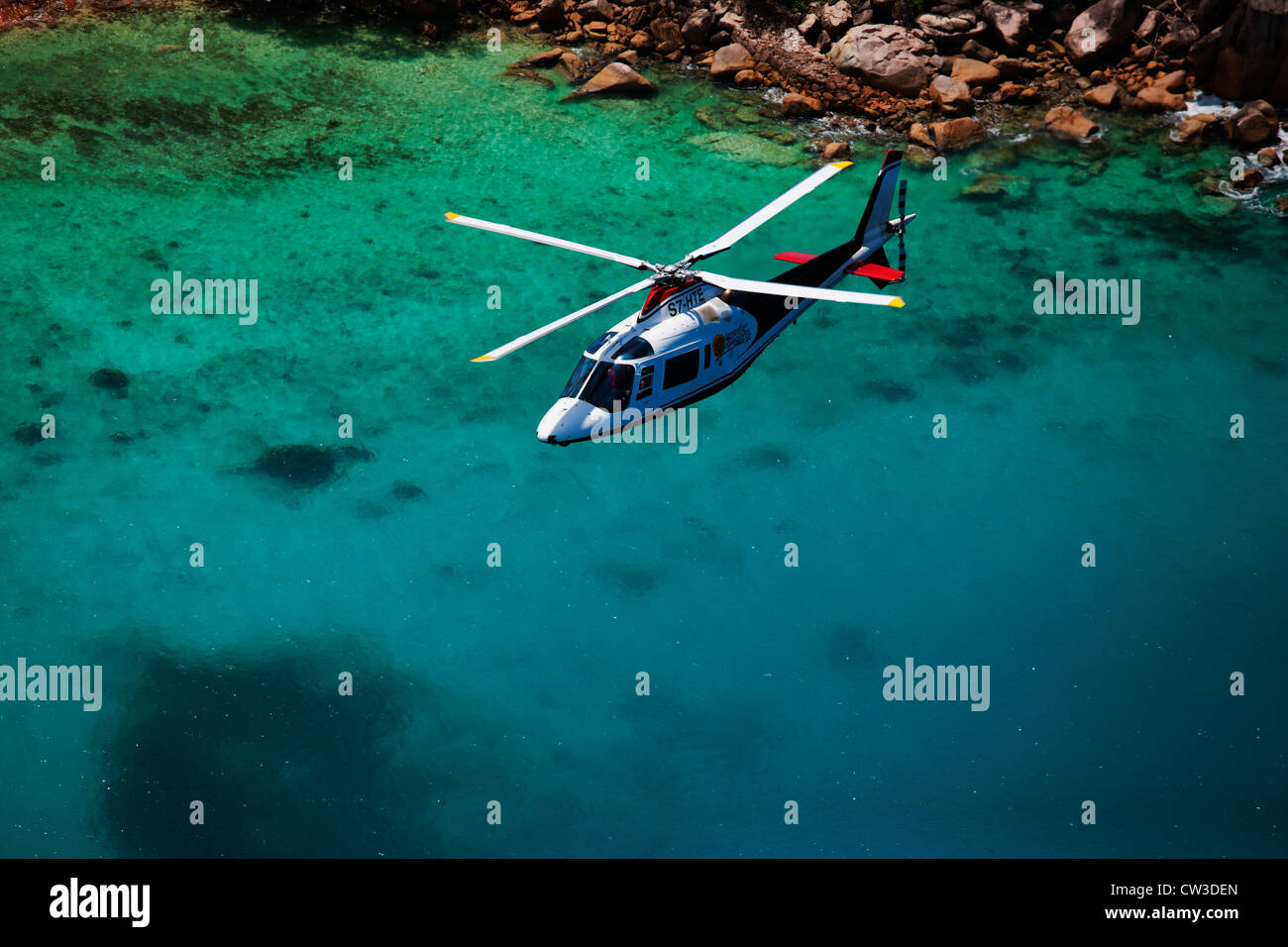 Agusta 109C Helicopter flying over the coast of Praslin.Seychelles - Stock Image