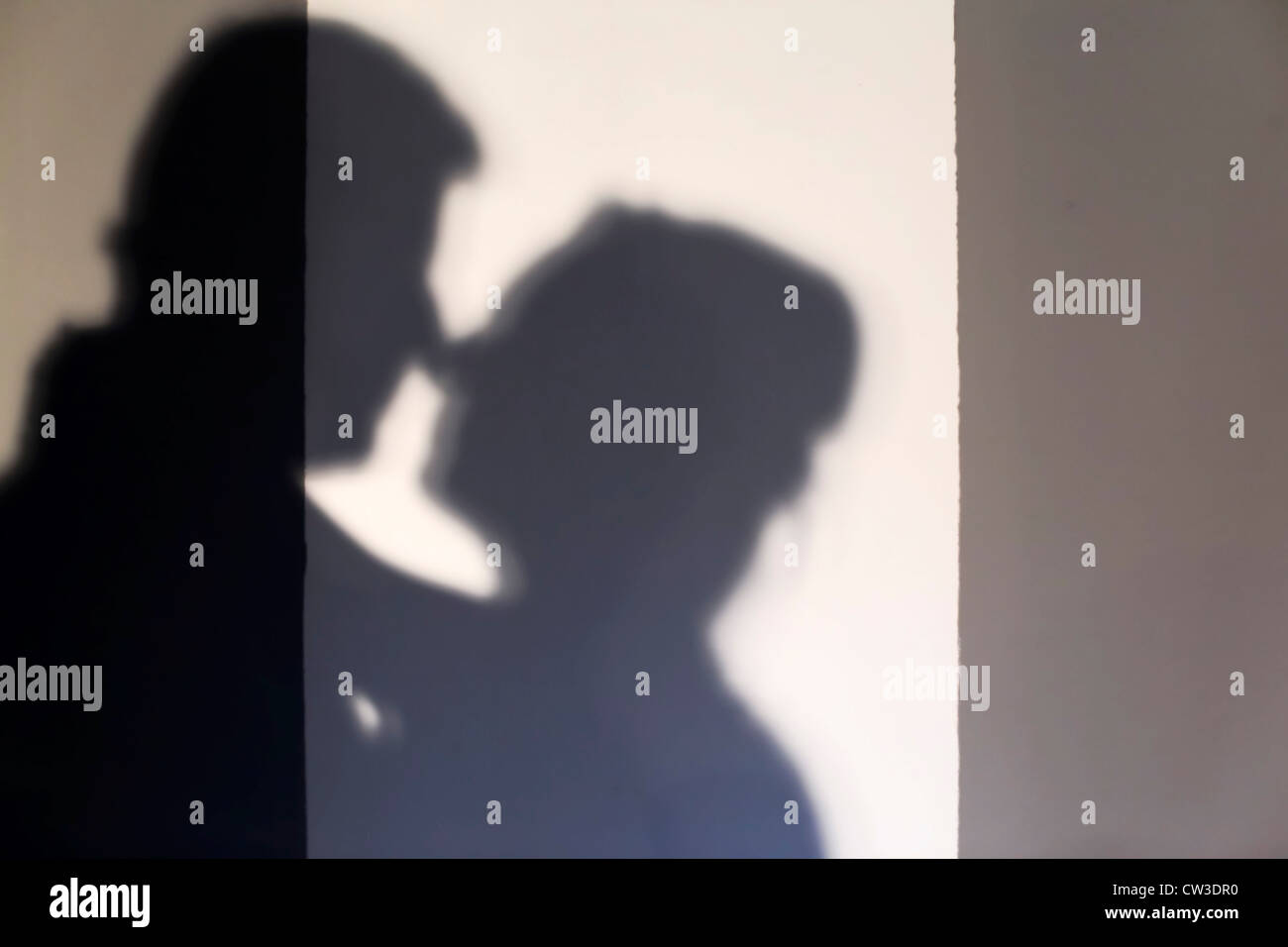 Silhouette of a kissing couple - Stock Image