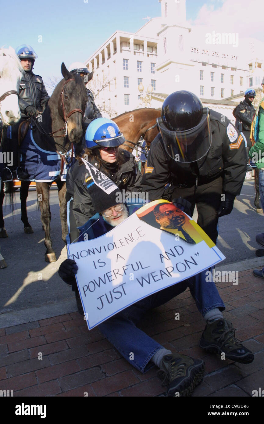 """US Park Police clear the streets of a sitting protester wearing a sign reading """"Nonviolence is a Powerful and Just Stock Photo"""