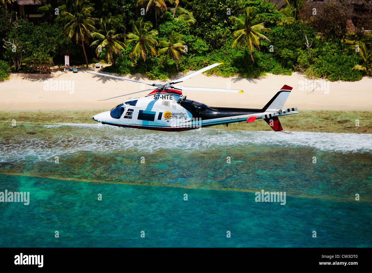 Agusta 109C Helicopter flying over the coast of Praslin.Seychelles. - Stock Image