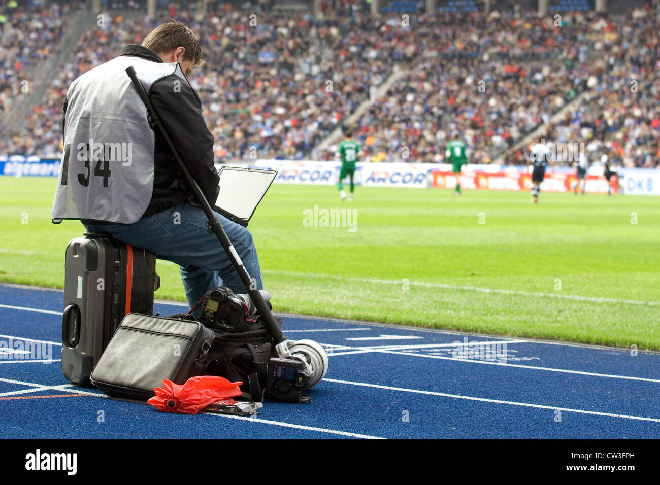 Berlin, a sports journalist at a football match on the sidelines - Stock Image