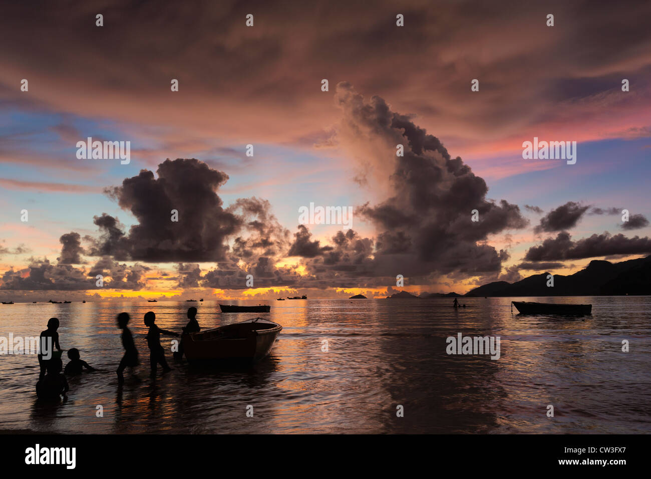 Fishing boats with children at sunset on a secluded beach. Mahe Seychelles - Stock Image
