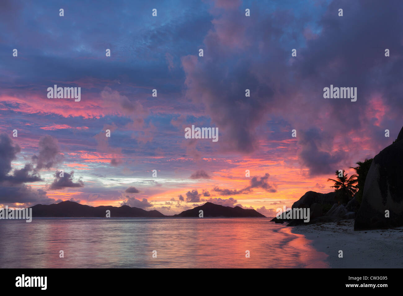 View of beach at sunset with granite boulders.La Digue Island. Seychelles. - Stock Image
