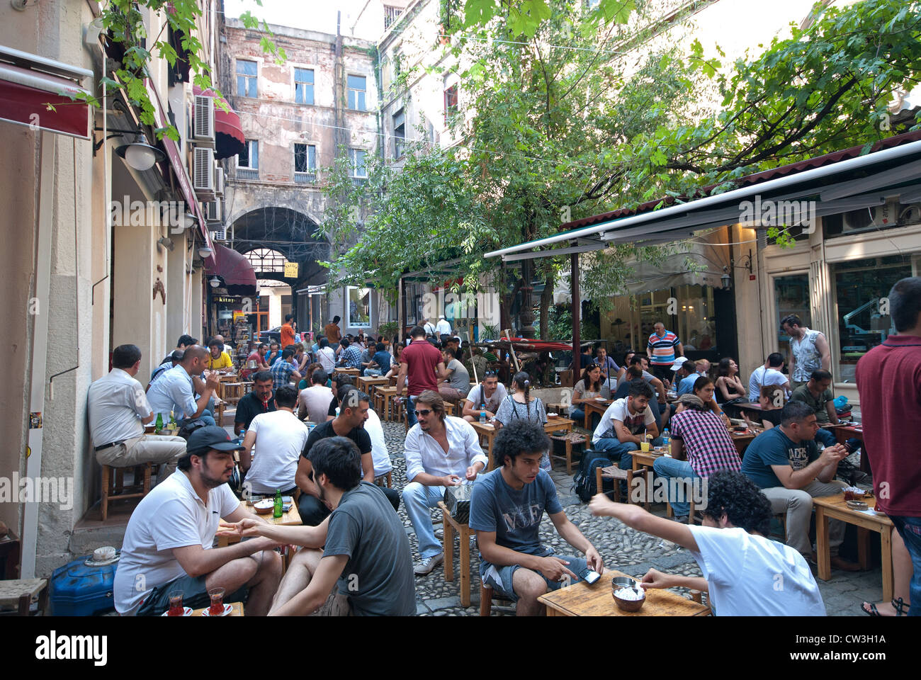 ISTANBUL, TURKEY. Young Turkish people at a street cafe off Istiklal Caddesi in the Beyoglu district of the city. - Stock Image