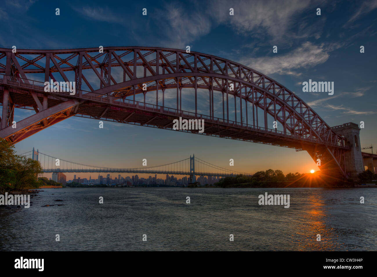 The Hell Gate and Triborough Bridges span the Hell Gate tidal strait in the East River during sunset in New York - Stock Image