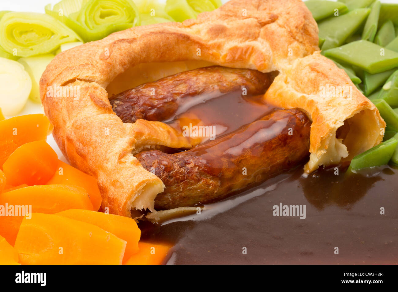 Classic British dinner of Toad in the Hole with vegetables and thick gravy - studio shot - Stock Image