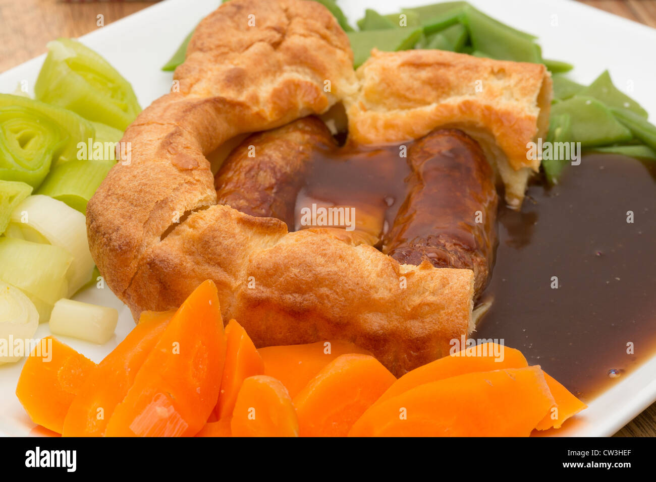 A classic British dish of Toad in the Hole, which are pork sausages cooked in batter then served with vegetables - Stock Image