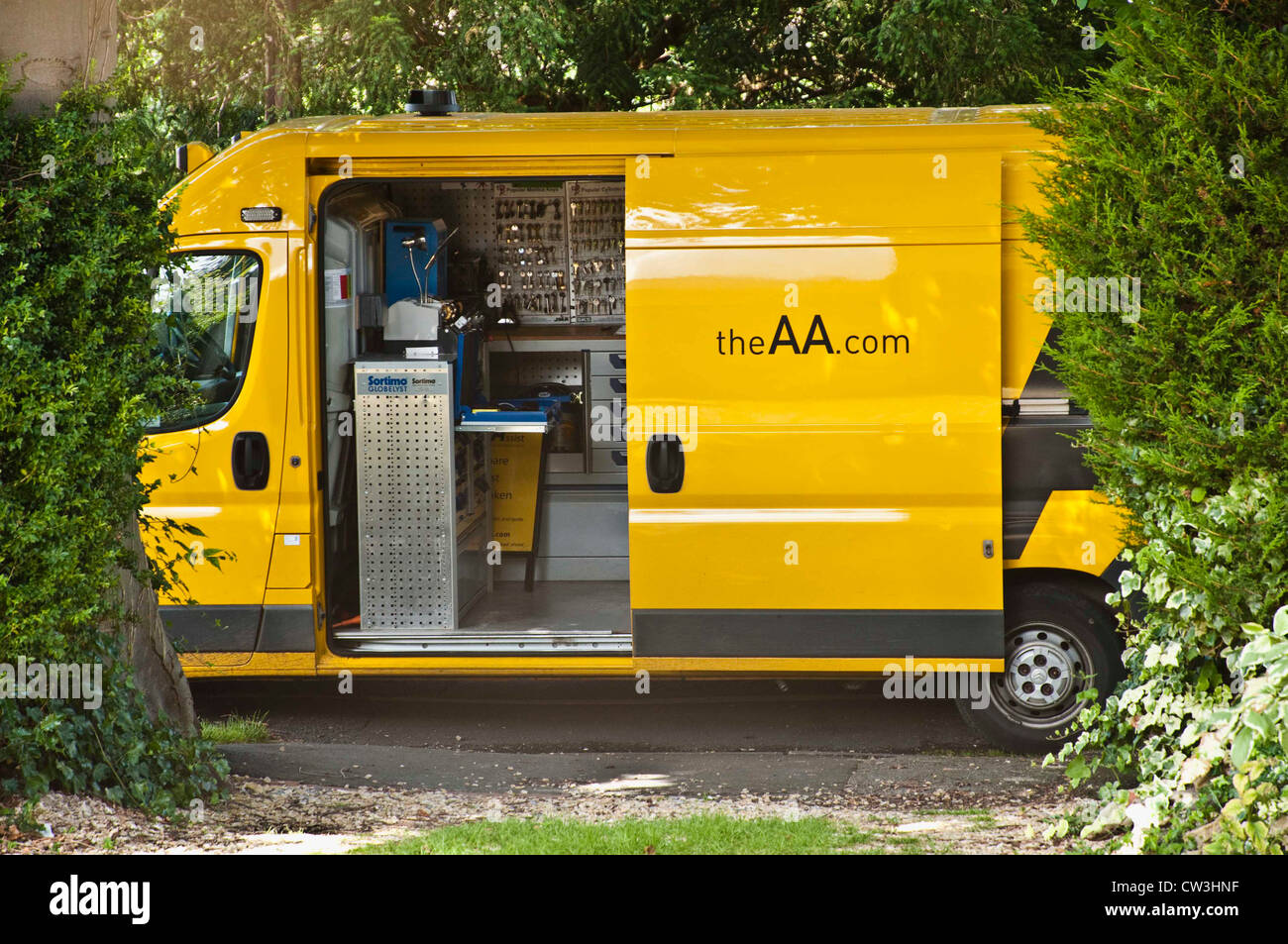 An AA van converted to provide a  mobile car key cutting service.  Shown parked outside a house. UK. - Stock Image