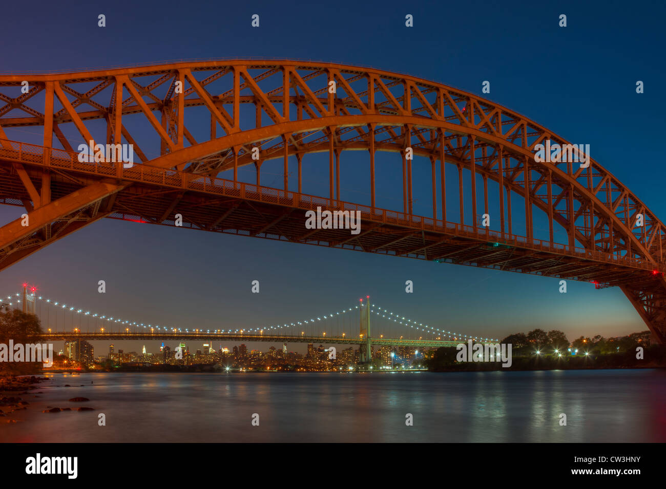 The Hell Gate and Triborough Bridges span the Hell Gate tidal strait in the East River during evening twilight in - Stock Image