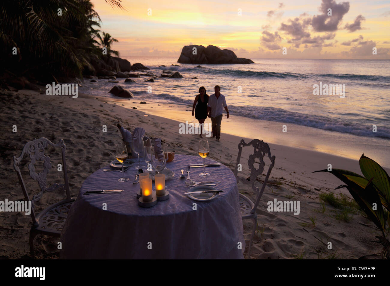 Romantic couple walking at sunset on beach with dinner table in foreground.Cousine Island.Seychelles - Stock Image