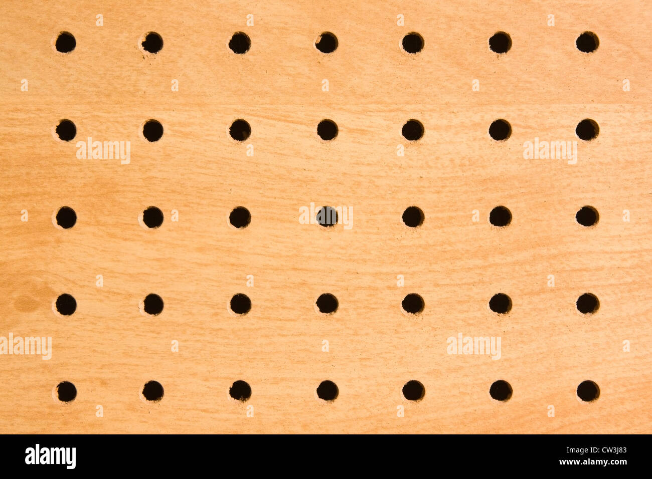Pegboard holes used for hanging and storing tools. - Stock Image