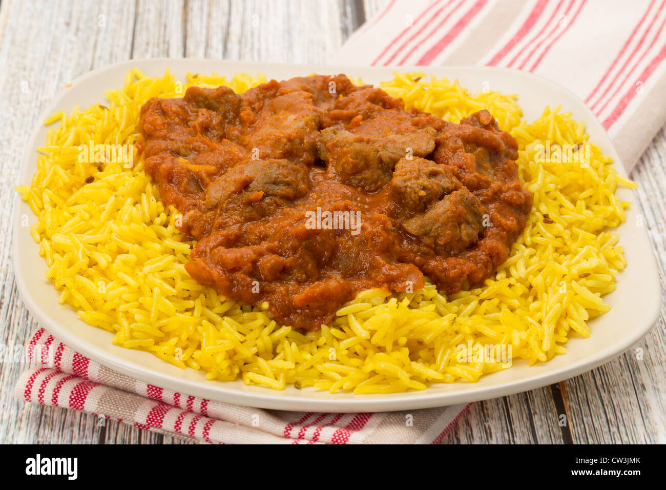 Indian meal of lamb rogan josh served with fragrant pilau rice - Studio shot - Stock Image