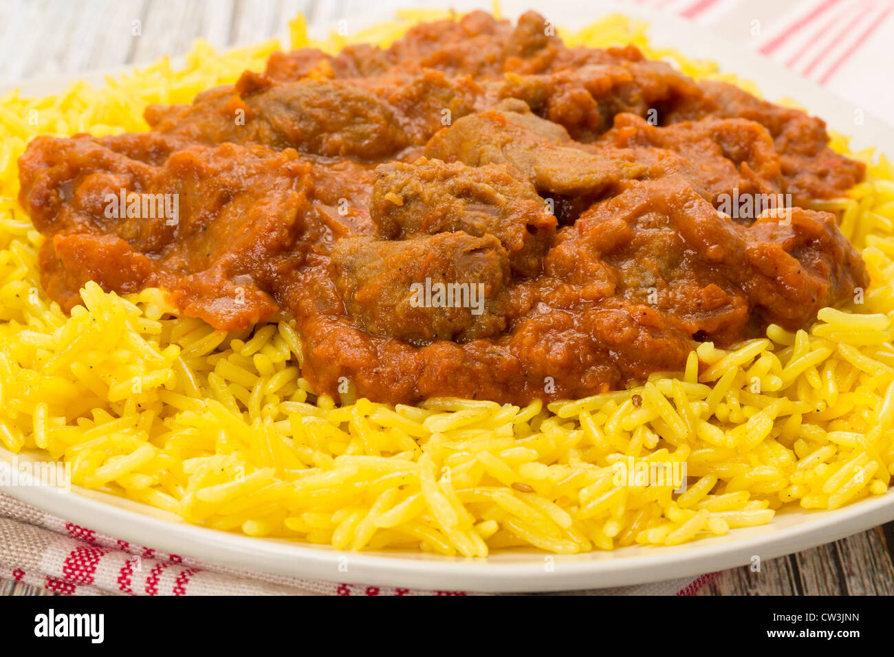 close-up shot of an Indian meal of lamb rogan josh served with fragrant pilau rice - Studio shot - Stock Image