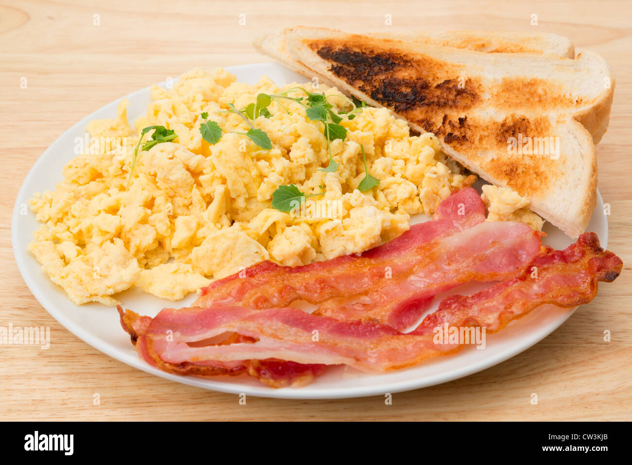 Scrambled eggs with streaky bacon breakfast with slices of toast - studio shot - Stock Image