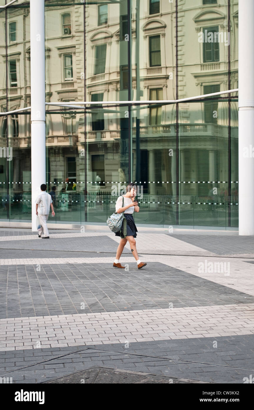 Young woman walking in front of Imperial College, Exhibition Road, South Kensington, London, UK Stock Photo