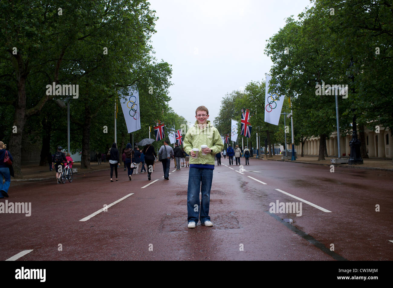 Supporter standing on wet day at the London Olympics 2012 with Olympic flags - Stock Image