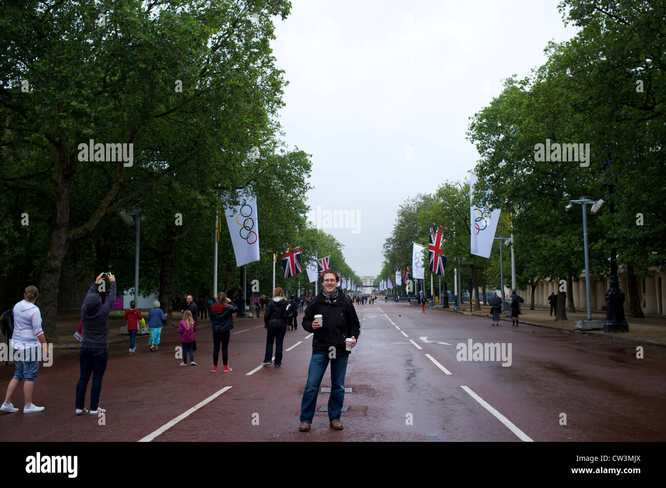 Supporter on wet day at the London Olympics 2012 with Olympic flags - Stock Image