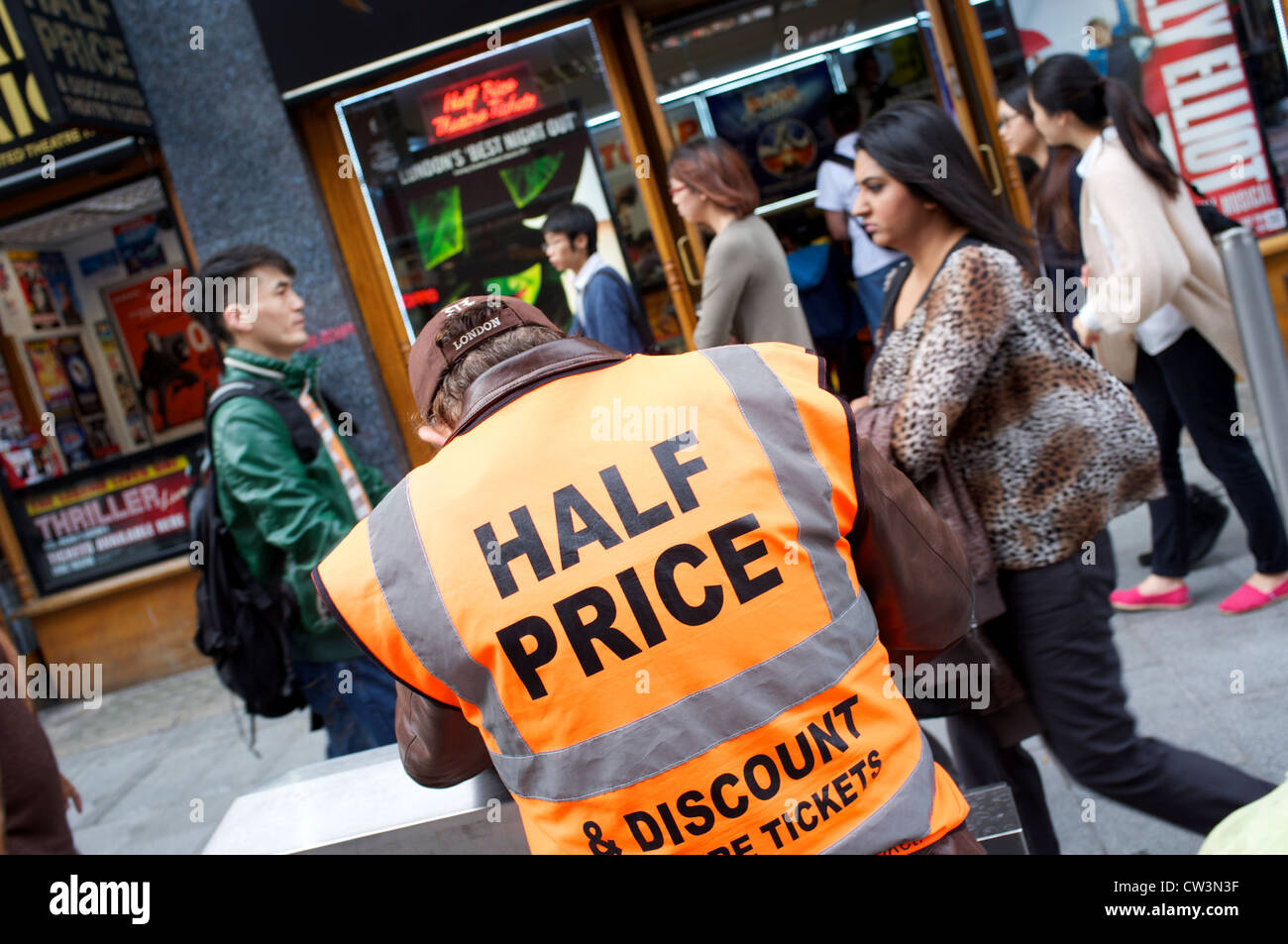 Man wearing a hi vis jacket with Half Price written on it, discounts, London - Stock Image