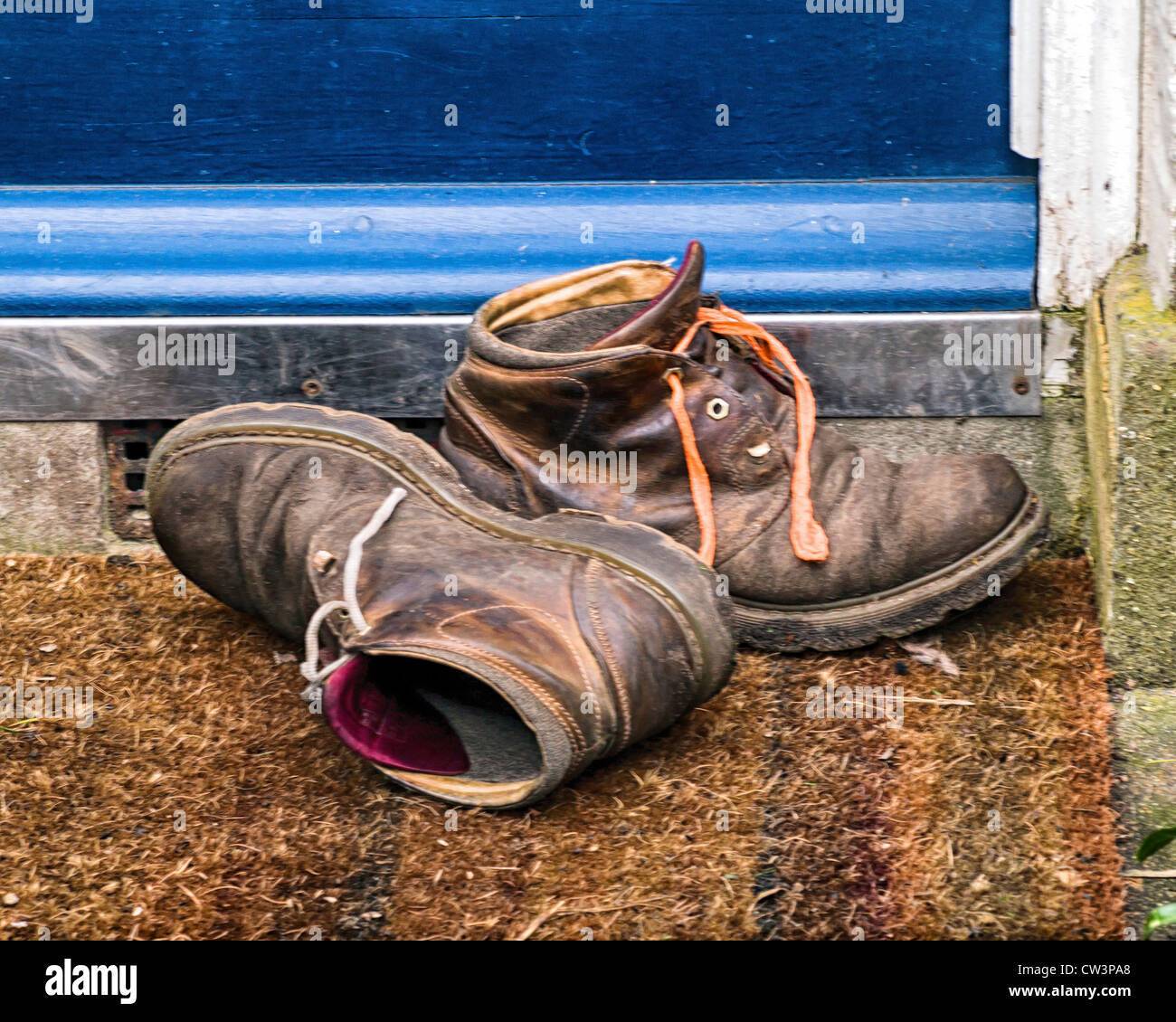 Dirty working boots with mismatched laces are left on a mat outside a front door - Stock Image
