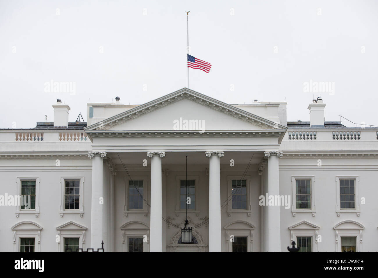 The White House with its flag lowered to half mast. - Stock Image