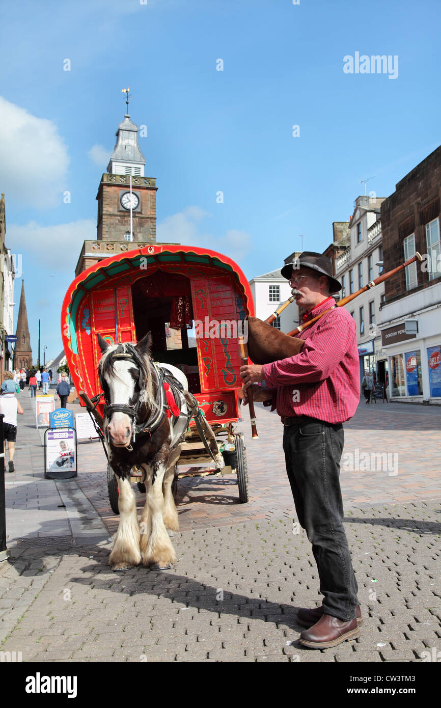 Man playing pipes in front of Gypsy style horse drawn caravan at Dumfries, Scotland, UK - Stock Image