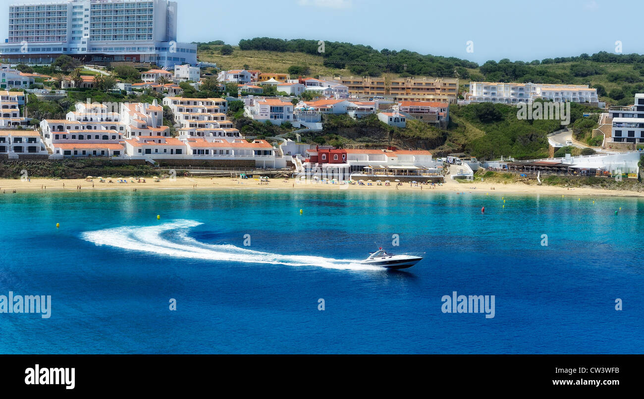 A speedboat turns and leaves the bay in arenal d'en castell menorca spain - Stock Image