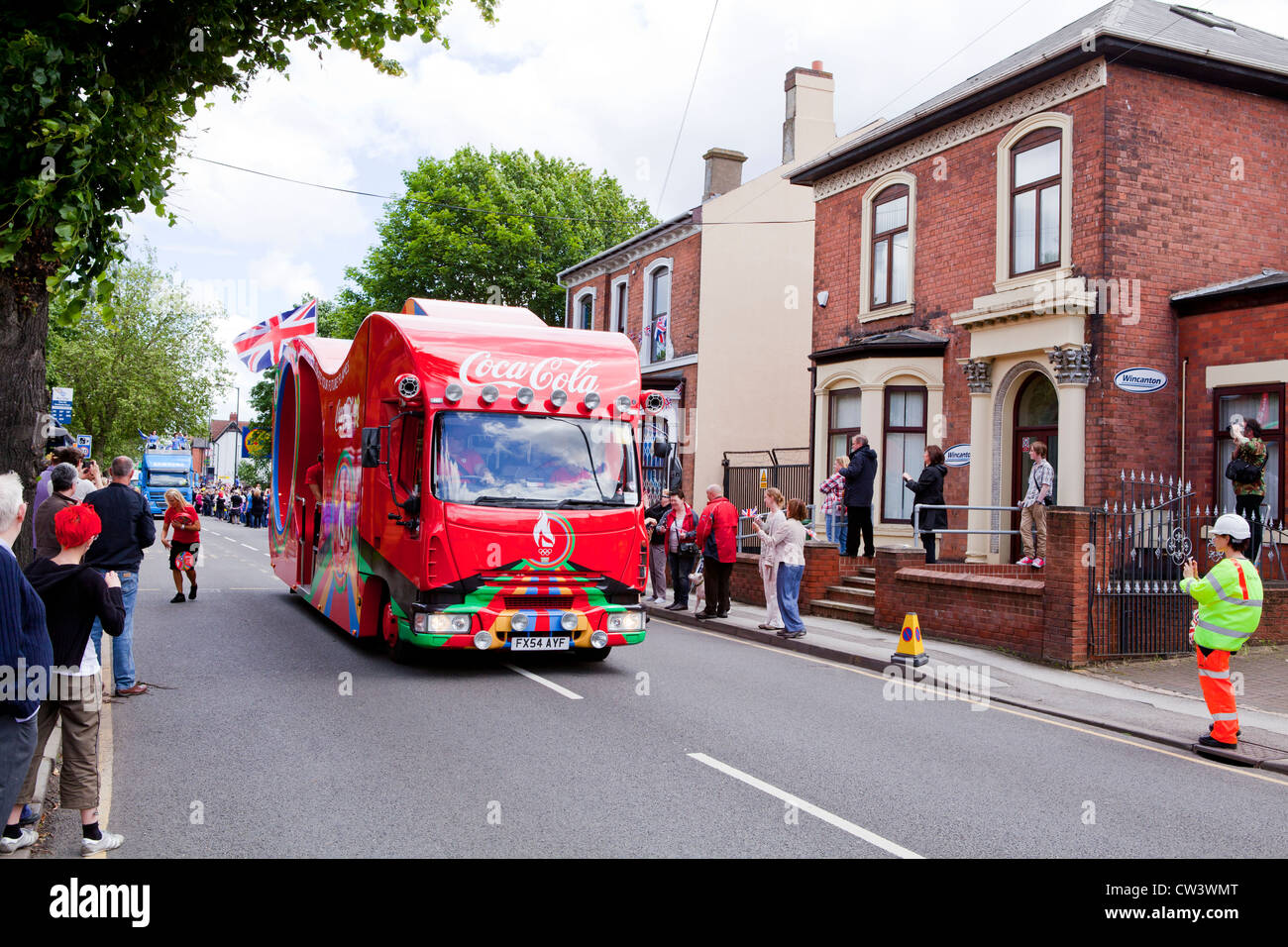 Crowds line New Road, Willenhall, West Midlands to await the passing of the Olympic Torch and its bearer preceded - Stock Image
