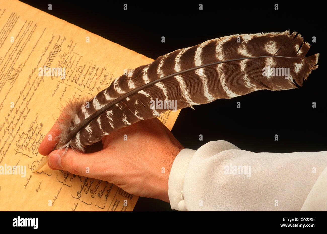 Hand holding quill pen signing U.S. Constitution - Stock Image