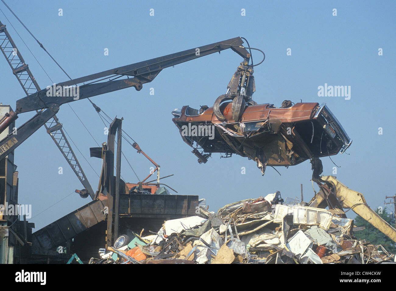 A wrecking crane lowering a demolished automobile onto a pile of junk, Atlanta, Georgia - Stock Image