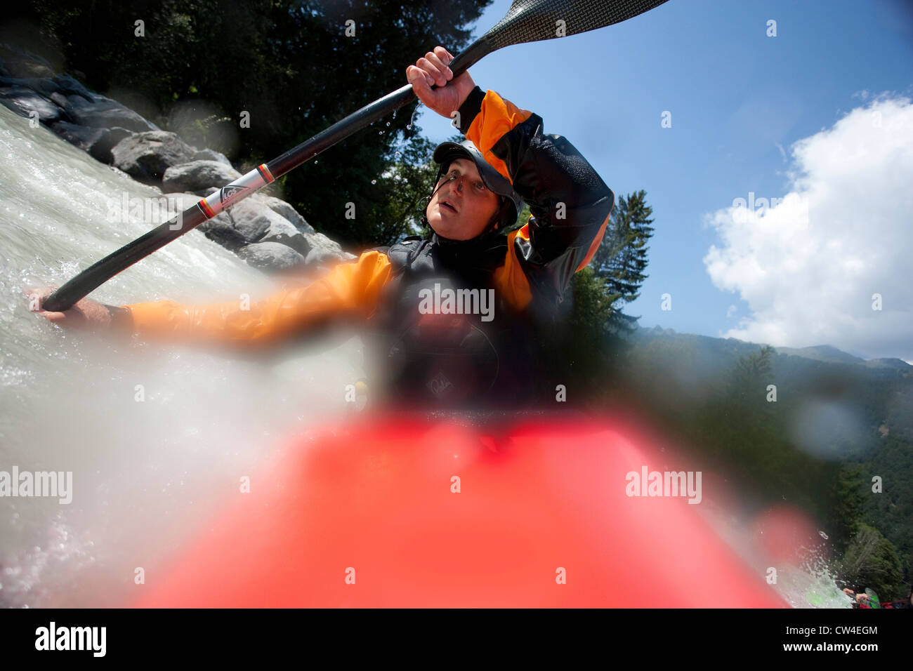 Whitewater kayaker turning into an eddy on Inn River near Pfunds, Austria - Stock Image