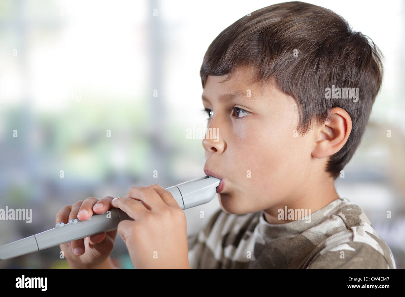 A young boy plays a recorder with concentration - shallow depth of field with copy space to left - Stock Image