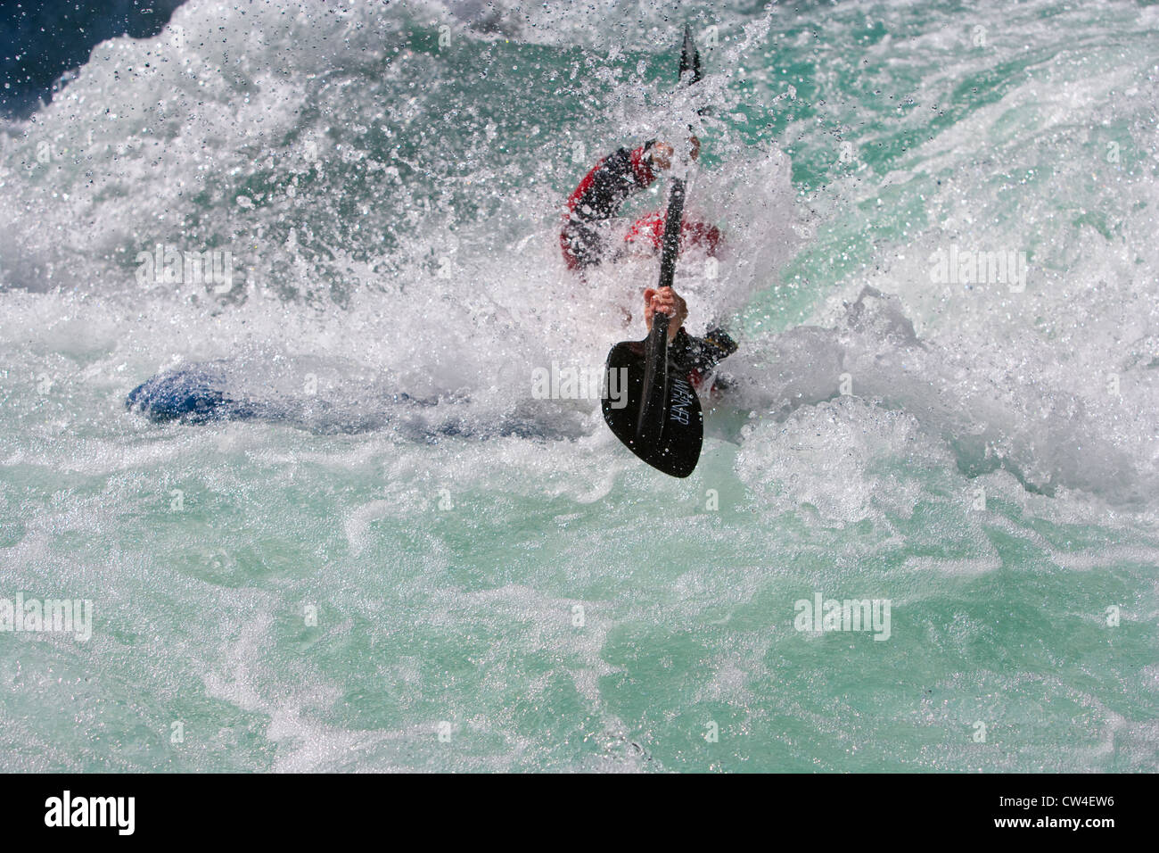 Whitewater kayaker surfacing after running drop on Inn River near Pfunds, Austria - Stock Image