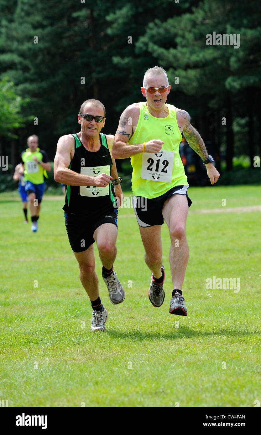 Two male runners dashing for the finish line. - Stock Image