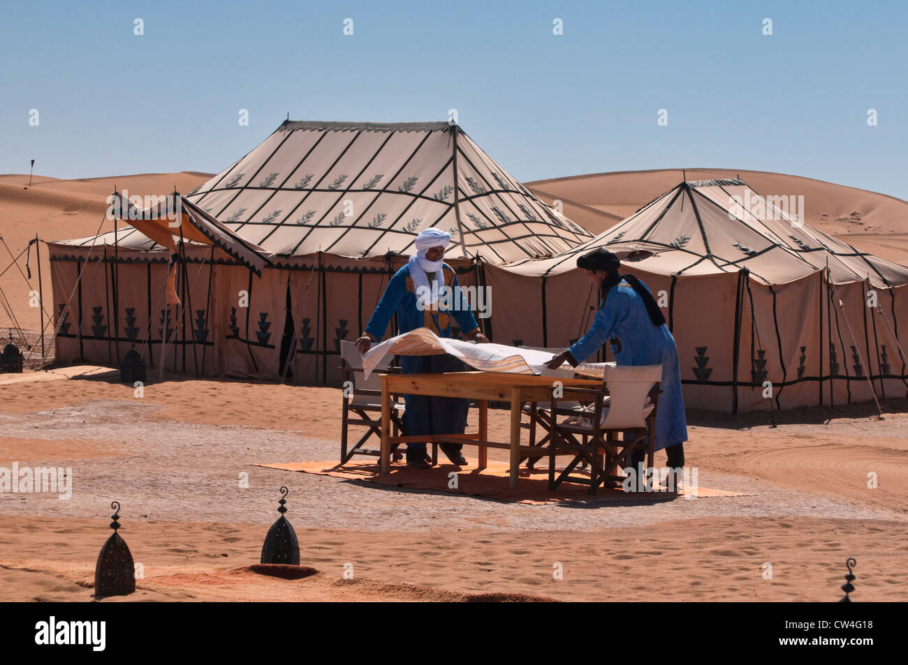 Berbers set the table at a luxury desert camp in the Sahara at Erg Chigaga, Morocco - Stock Image