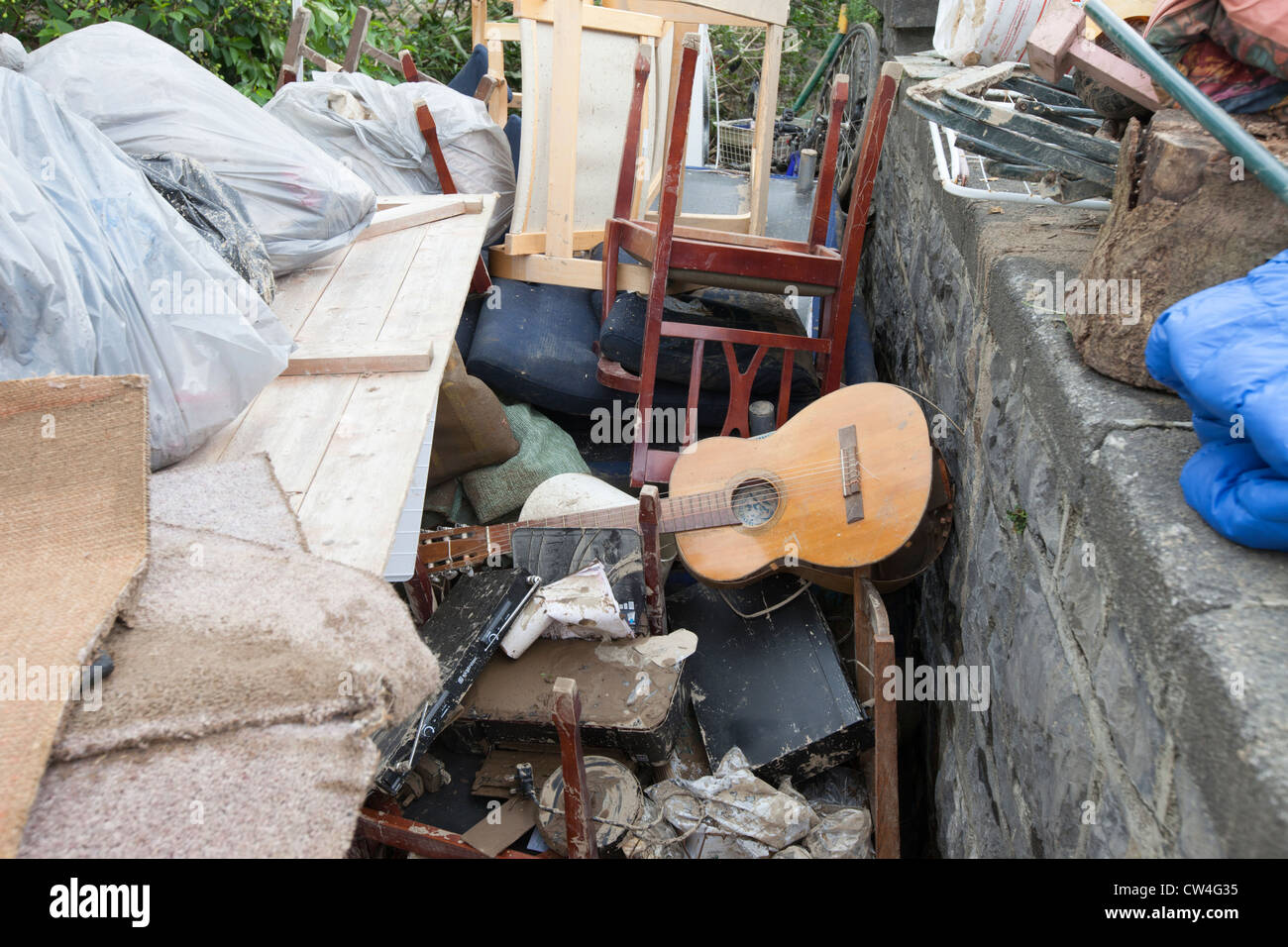Ruined possessions piled high outside a property in Talybont which was hit by flash flooding. - Stock Image