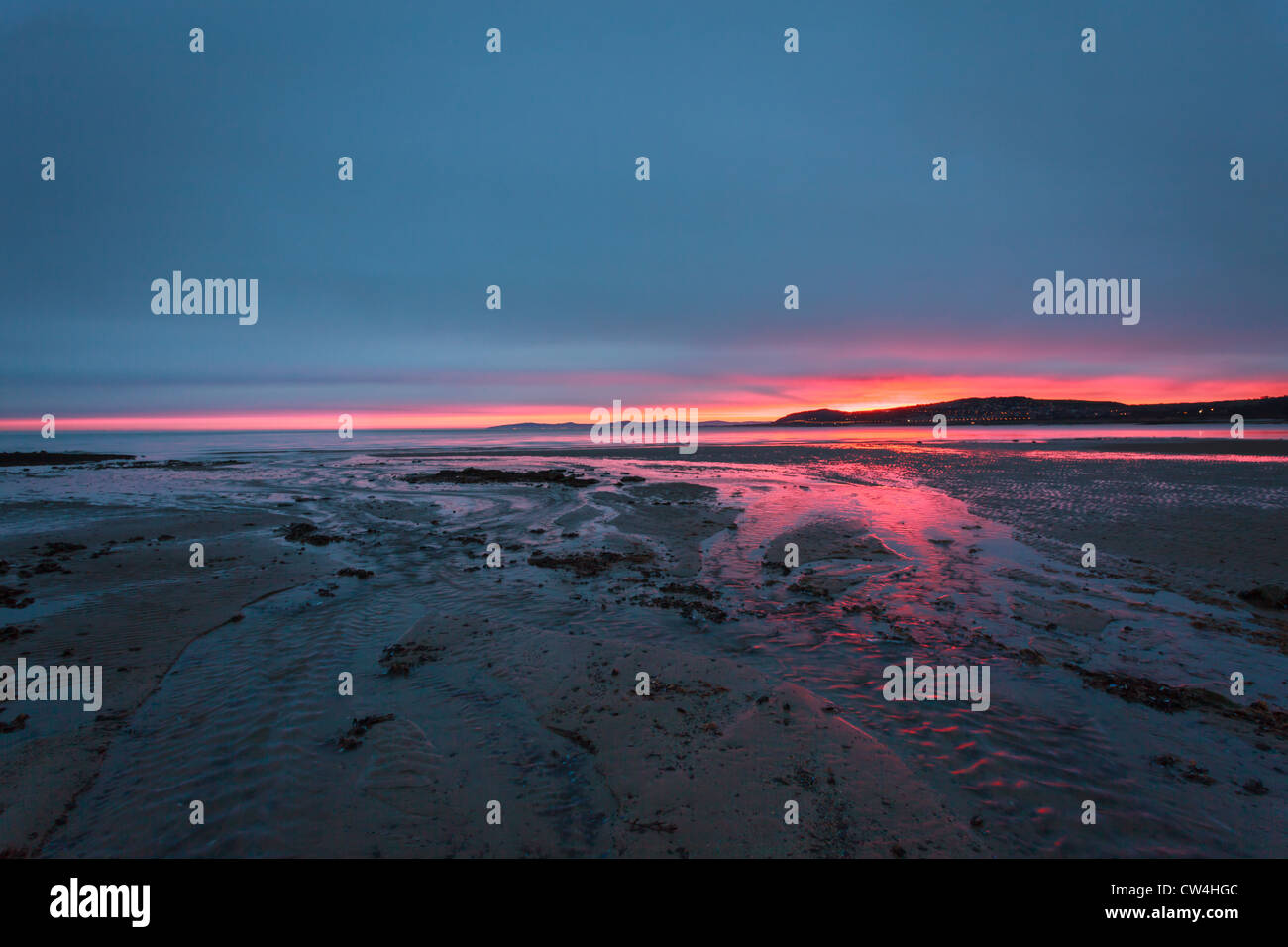 Sunrise over a beach in Wales showing red sky - Stock Image
